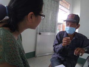 Dinh Thi Nhung, a research assistant for the Woolcock Institute, speaks to a tuberculosis patient who completed six months of treatment but was unable to afford an x-ray that would tell him if he had cleared the infectious organism from his lungs.