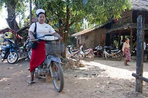 Senior midwife attends to her malaria and primary health patients by motorbike. This is often the only mode of transport for the uneven roads she has to use to reach her remote communities in the Thanintharyi region, southern Myanmar. 2011. Photo: James Howlett, 3DFund.org DFAT, Flickr
